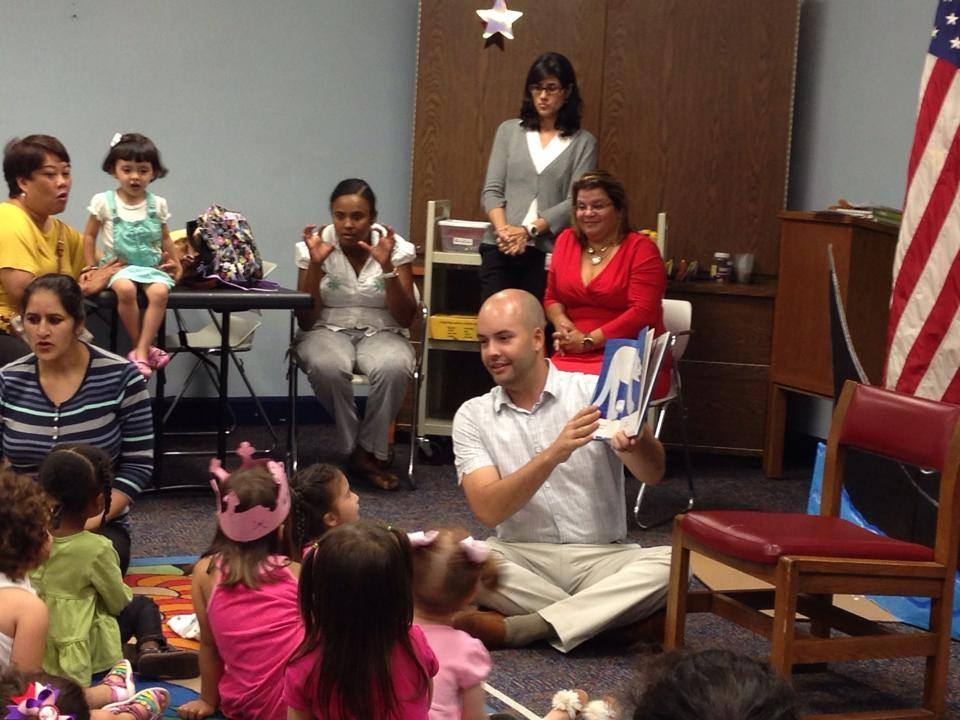 Manny reading books to children at the Miami Lakes branch Library